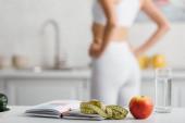 Selektiver Fokus von Notizbuch, Maßband und Apfel auf dem Tisch mit Sportlerin in der Küche