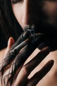 Szelektív fókusz lány fekete festett kézzel és ajkak dohányzás cigaretta elszigetelt fekete