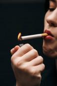 Fotografie abgeschnittene Ansicht einer Frau, die sich Zigarette mit Feuerzeug anzündet, isoliert auf schwarz