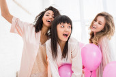 excited multicultural girls having bachelorette party with pink balloons