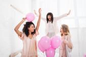 vonzó boldog multikulturális barátnők tánc és ugrás az ágyban rózsaszín lufik leánybúcsú