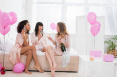 multietnické dívky se šampaňským mluvící na rozlučce se svobodou s balónky