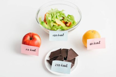Fresh fruits, chocolate and salad with calories on cards on white background, calorie counting diet