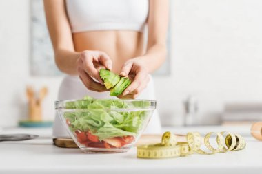 Cropped view of slim woman cooking salad with fresh vegetables and avocado near measuring tape on kitchen table