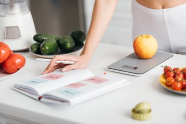 Selective focus of woman writing calories while weighing apple near fresh vegetables on kitchen table, calorie counting diet