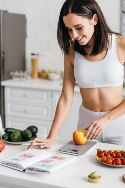 Selective focus of beautiful smiling sportswoman writing calories while weighing apple on kitchen table, calorie counting diet