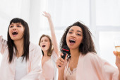 beautiful smiling multicultural girls singing with microphone on pajama party