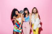 Fotografie sexy multikulturelle Freundinnen mit Champagner und Discokugel posieren auf rosa