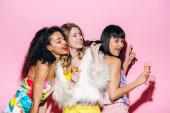 vidám multikulturális barátnők kezében pezsgős poharak és disco labda, miközben énekel mikrofonnal rózsaszín