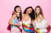 smiling stylish multiethnic girls holding glasses with milkshakes on pink