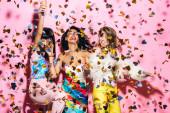 šťastné multikulturní dívky baví s sklenicemi šampaňského na růžové s konfety