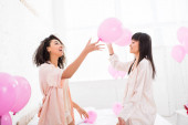 emotional multicultural girls in bathrobes holding pink balloons on bachelorette party