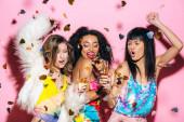 Fotografie aufgeregte multikulturelle Mädchen tanzen mit Champagnergläsern auf rosa mit Konfetti