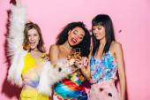 Fotografie fröhliche multikulturelle Mädchen amüsieren sich mit Sektgläsern auf rosa mit Konfetti