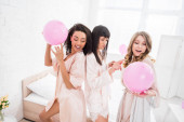 mosolygós multikulturális lányok táncolnak rózsaszín lufikkal lánybúcsún