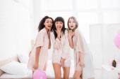 šokované multikulturní dívky v noční košili v ložnici s růžovými balónky