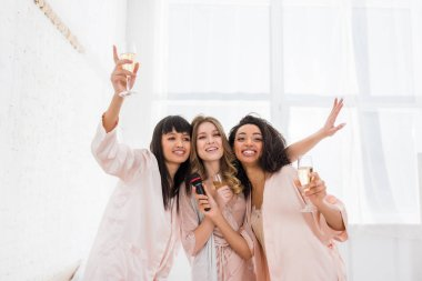 smiling multicultural girls holding champagne and singing with microphone on pajama party