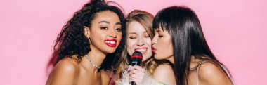 panoramic shot of cheerful multicultural girls singing karaoke with microphone, isolated on pink
