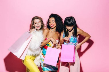 Emotional fashionable multiethnic girls posing with shopping bags on pink stock vector