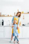 usmívající se matka objímající dceru a dívající se na kameru v kuchyni