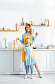 smiling mother holding hands with daughter and looking at camera in kitchen