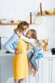oldalnézetben mosolygós lány ölelés anya a konyhában