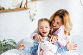 usmívající se matka ukazuje měkkou hračku šokované dceři v ložnici