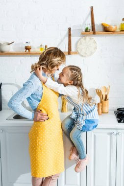 Side view of smiling daughter hugging mother in kitchen stock vector