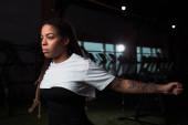 Afričanky americká žena strečink před tréninkem v tělocvičně