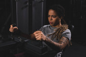 selective focus of tattooed african american girl with dreadlocks working out on fitness machine