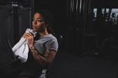 tetované africké Američanky drží ručník v blízkosti fitness stroje