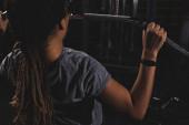 zpět pohled na mladé africké americké dívky s smartwatch školení v tělocvičně