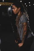 Seitenansicht eines afrikanisch-amerikanischen Mädchens mit Tätowierung beim Turnen im Fitnessstudio
