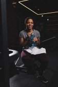 happy african american girl with tattoo holding sports bottle with water