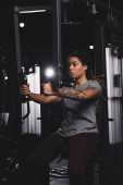 sportive african american girl with tattoo training on gym machine