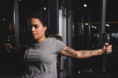 attractive african american girl with tattoo training on gym machine