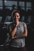 boldog afro-amerikai lány tetoválás nézi kamera tornaterem