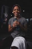 šťastná a potetovaná africká americká žena držící sportovní láhev