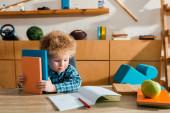 roztomilý chytrý kluk při pohledu na notebook a držení knih