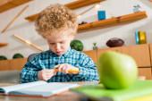 Selektiver Fokus des netten und intelligenten Kindes mit Stift in der Nähe von grünem Apfel