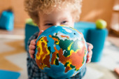 selective focus of smart kid covering face with globe