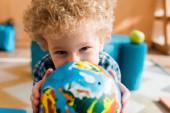 Selektiver Fokus des intelligenten Kindes mit Globus und Kamera