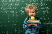 vidám gyerek kezében könyvek és alma közelében kréta matematikai képletek