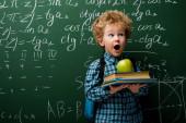 překvapené dítě drží knihy a jablko v blízkosti tabuli s matematickými vzorci