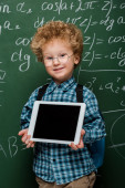 Photo cheerful kid in glasses holding digital tablet with blank screen near chalkboard with mathematical formulas