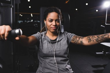 selective focus of happy and tattooed african american woman listening music in gym