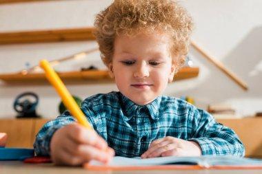 Selective focus of smart kid writing in notebook stock vector