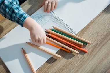 Top view of kid taking orange pencil stock vector