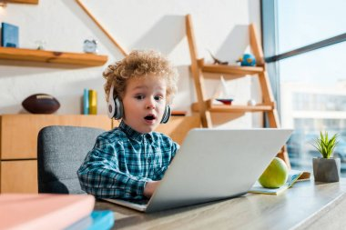 selective focus of surprised kid typing on laptop near apple while listening music in wireless headphones