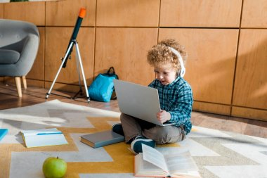 smart child in headphones using laptop near apple and books